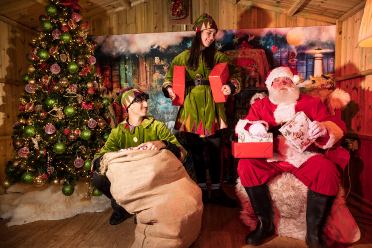Santa and 2 elves holding gifts and sat in front of a decorated Christmas Tree